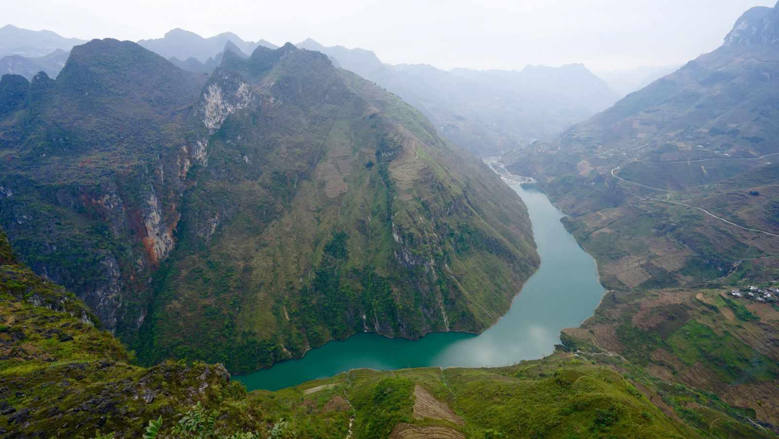 Từ trên đèo, bạn có thể nhìn thấy dòng Nho Quế mềm mại như một dải lụa giữa núi đồi. Tour du lich dong bac.